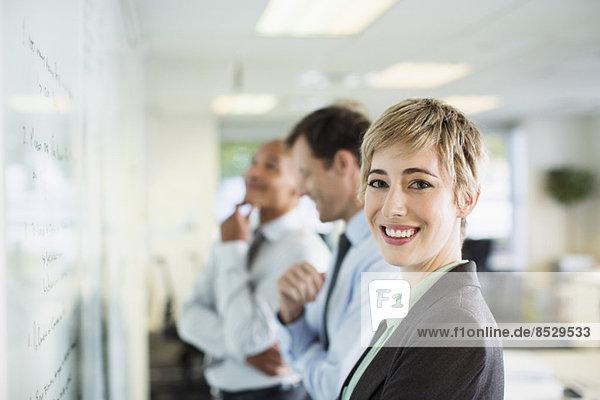 Geschäftsfrau lächelt über Whiteboard im Büro