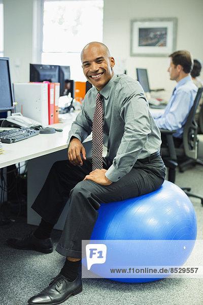 Geschäftsmann sitzend auf Fitnessball im Büro