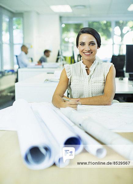 Geschäftsfrau mit Bauplänen im Büro