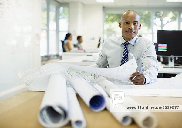 Geschäftsmann bei der Prüfung von Bauplänen im Büro