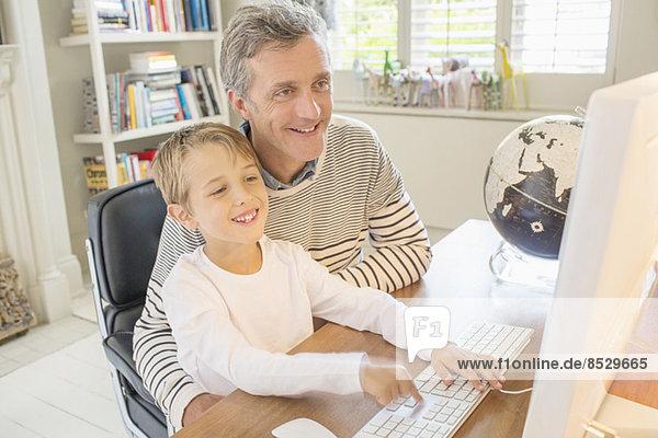 Vater und Sohn nutzen gemeinsam den Computer