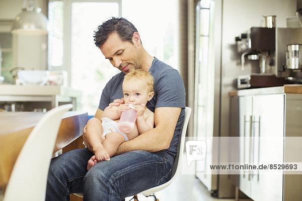 Vater füttert Baby in der Küche