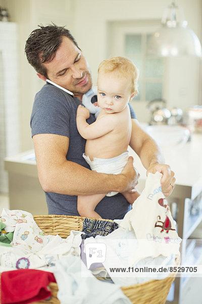 Vater hält Baby und faltet die Wäsche  während er am Handy spricht