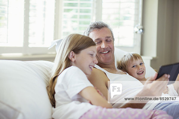 Father and children using digital tablet on bed