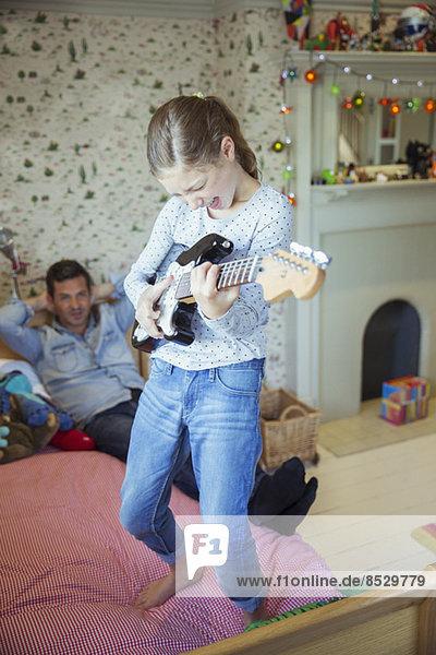 Mädchen spielt Gitarre für Vater im Schlafzimmer