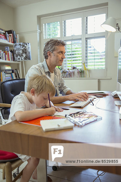 Vater und Sohn arbeiten im Home Office