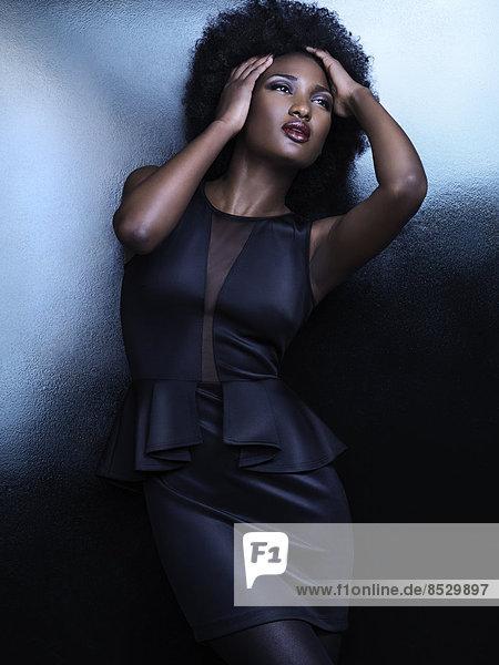 Frau in einem eleganten schwarzen glänzenden Kleid