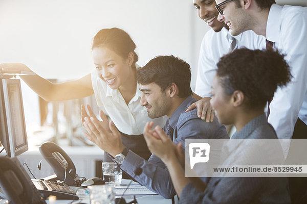 Geschäftsleute  die Computer im Büro anfeuern