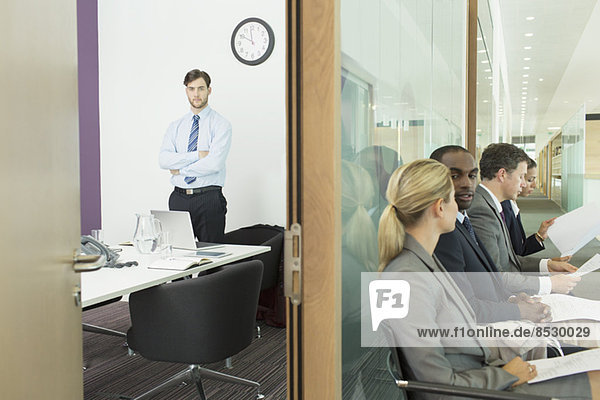 Geschäftsmann im Büro und Geschäftsleute im Flur