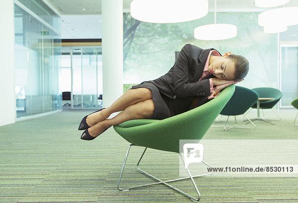 Geschäftsfrau schläft im Bürostuhl