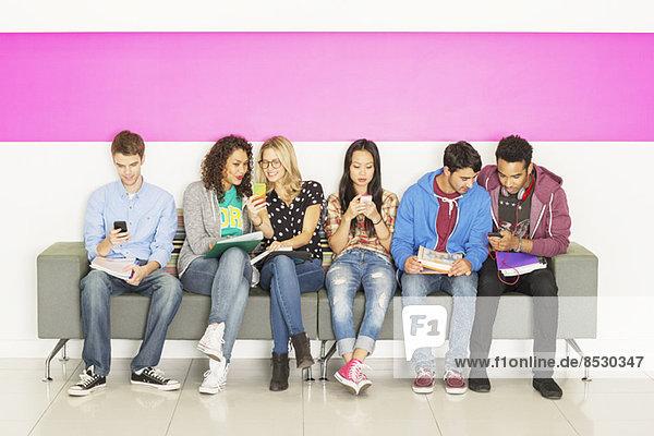 Universitätsstudenten sitzen auf der Bank