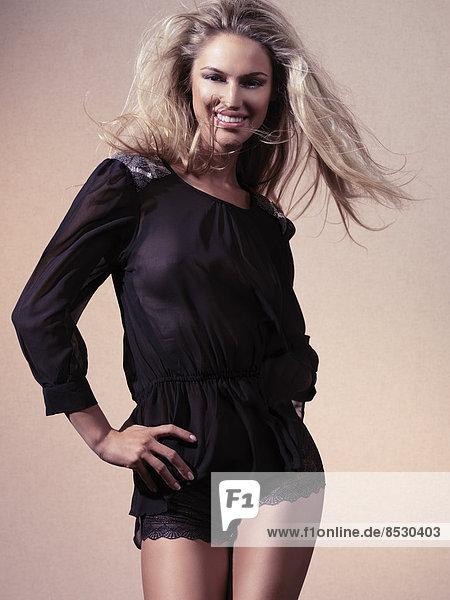 Frau mit fliegenden Haaren in schwarzen Spitzen-Shorts und einer durchsichtigen Bluse