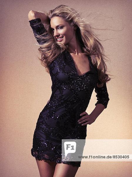 Lächelnde Frau mit langen fliegenden Haaren in einem schwarzen Kleid