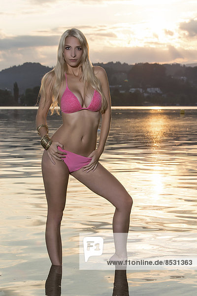 Frau im pinken Bikini steht an Seestrand bei Sonnenaufgang