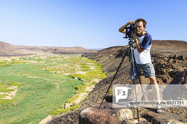 Photographer with a camera at the Huab River  Damaraland  Namibia