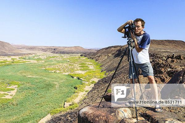 Fotograf mit Kamera am Fluss Huab  Damaraland  Namibia