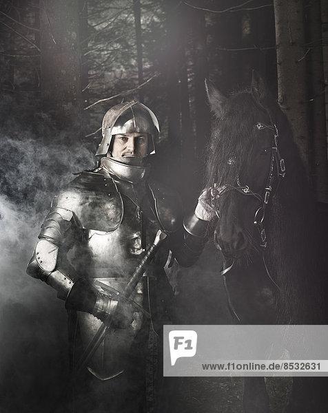 Ritter mit Ritterrüstung steht mit seinem Pferd im Wald  Tirol  Österreich Ritter mit Ritterrüstung steht mit seinem Pferd im Wald, Tirol, Österreich