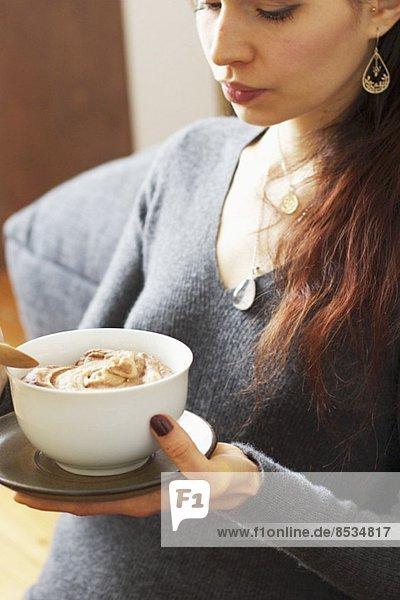 Frau hält Schälchen mit Pastinakencreme