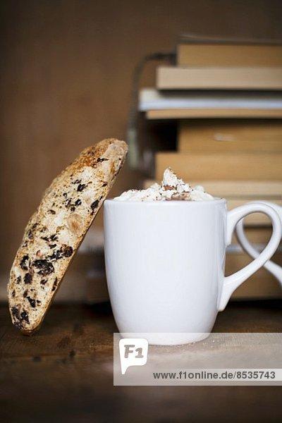 Heisse Schokolade mit Biscotti vor einem Bücherstapel