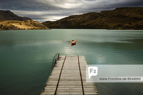 Ein junger Mann in der Luft  der von einem Holzsteg in einen ruhigen  von Bergen umgebenen See im Nationalpark Torres del Paine in Chile springt.