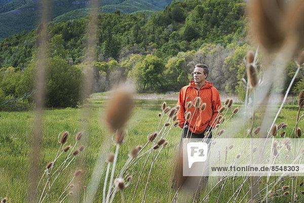 Ein Mann in orangefarbener Jacke geht auf seinem Grundstück spazieren.