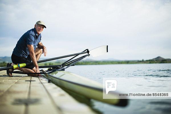 Mann  reifer Erwachsene  reife Erwachsene  Außenaufnahme  Vorbereitung  Boot  Steg  Rudern