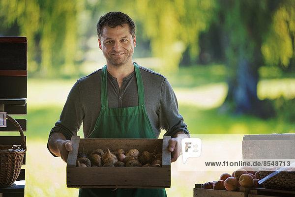 Ein Mann mit einer Kiste frisch gepflückter Früchte.
