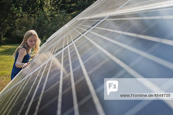 Ein junges Mädchen  das neben einer großen Solarzellenanlage steht und sich an sie lehnt.