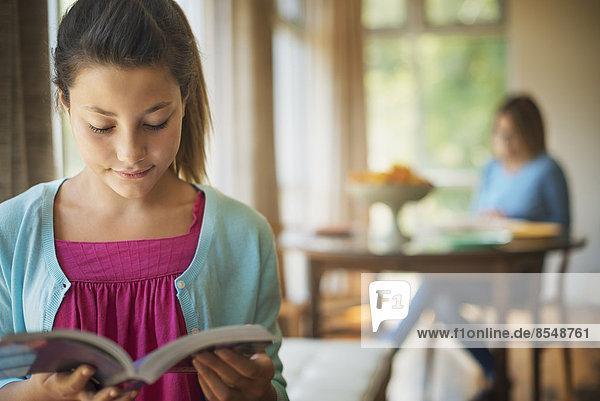 Eine junge Frau liest ein Buch  in einem traditionell eingerichteten Haus.