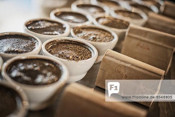 Das Probenahmeverfahren in einem Schuppen für die Kaffeeverarbeitung  wo das Personal Kaffee in kleinen Kannen zubereitet und eine Geschmacksprobe entnimmt  um die Mischung zu testen.