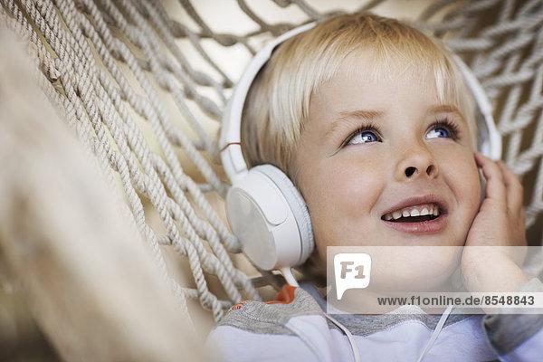 Ein kleiner Junge liegt in einer Hängematte und trägt Musikkopfhörer.