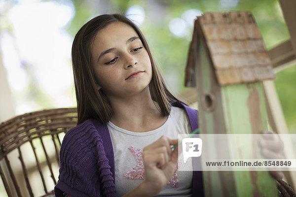 Ein Kind untersucht einen Wanzenkasten auf einer Veranda.