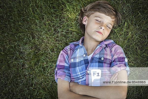 Ein Junge mit verschränkten Armen auf dem Gras liegend  die Augen geschlossen.