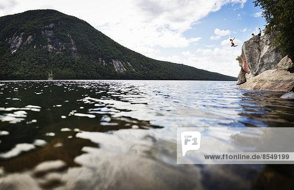 Eine Gruppe junger Leute springt von einer Klippe in das stille Wasser eines Sees.