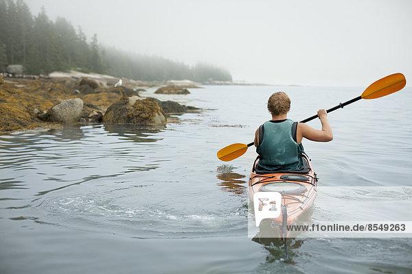 Ein Mann paddelt mit einem Kajak auf ruhigem Wasser bei Nebel. Bundesstaat New York  USA
