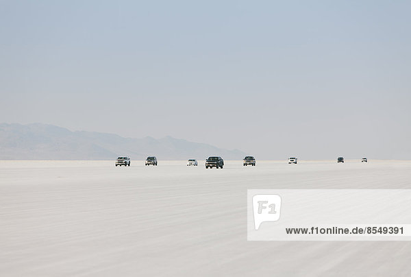 Autos fahren auf den Bonneville Salt Flats während der Speed Week. Abenddämmerung.