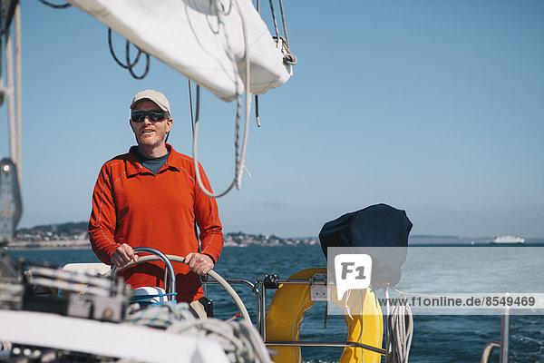 Mann mittleren Alters steuert Segelboot auf dem Puget Sound  Washington  USA