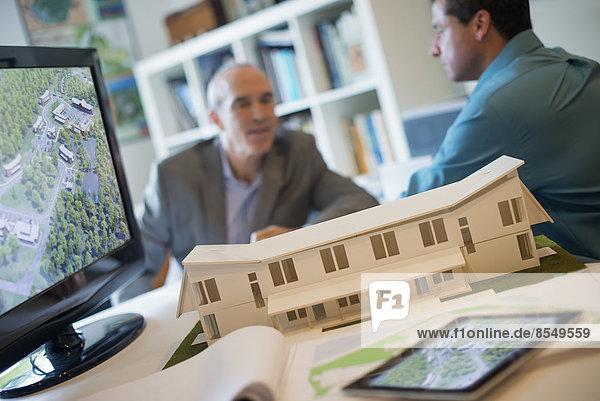 Architekten  die in einem Büro unter Einsatz von Computertechnologie an einem grünen Bauprojekt arbeiten. Maßstabsgetreues Modell eines Gebäudes.