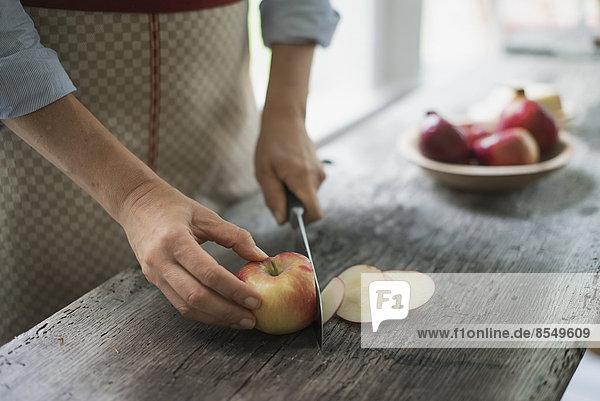 Eine Person  die einen Bio-Apfel zerschneidet.