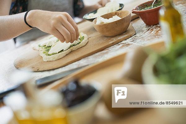 Eine Person  die einen Wrap mit frischen Zutaten und grüner Salsa macht.