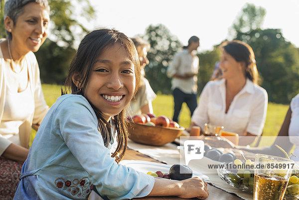 Eine Familie und Freunde bei einer Mahlzeit im Freien. Ein Picknick oder Buffet am frühen Abend.