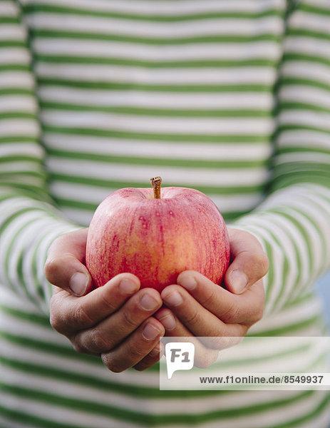 Detail eines neunjährigen Mädchens mit Bio-Apfel