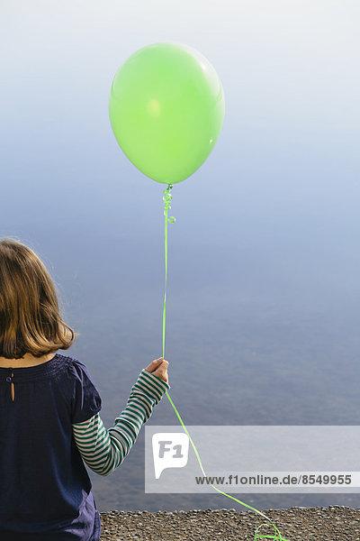 Neunjähriges Mädchen hält grünen Ballon in der Hand und sitzt am Wasser