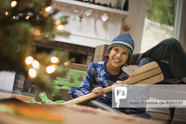 Ein Junge an einem Weihnachtsbaum  der ein Geschenk auspackt  ein hölzernes Ruder.