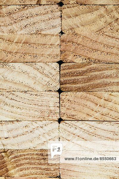 Stapel von vorbereitetem Schnittholz  Fichtenholzbrettern oder -stollen  zur Verwendung. Behandeltes Holz in traditionellen 2 x 4 gemessenen Schnittformen. Geschnittene Enden.