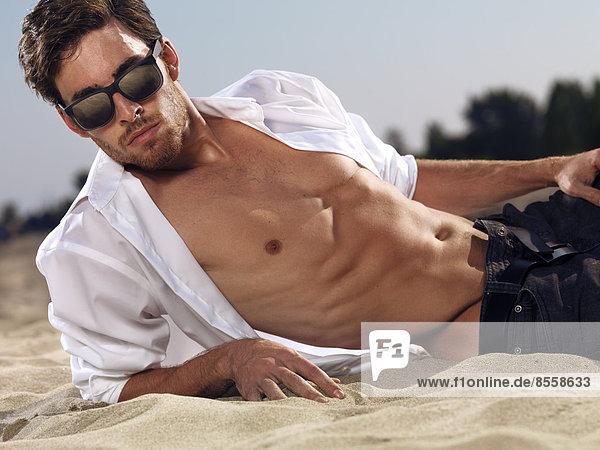 Mann mit Sonnenbrille und in aufgeknöpftem Hemd liegt am Strand