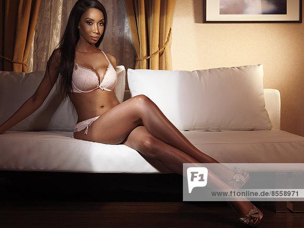 Woman wearing lingerie sitting on sofa