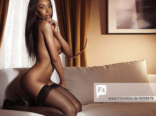 Halbakt  halbnackte Frau sitzt auf einem Sofa