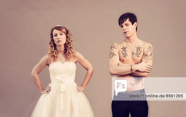 Hochzeitsfoto  Braut und Bräutigam  er mit nacktem Oberkörper  Tätowierungen und Zigarette