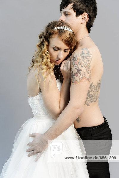 Hochzeitsfoto  Braut und Bräutigam  er mit nacktem Oberkörper mit Tätowierungen